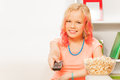 Girl holding remote control and bowl with popcorn Royalty Free Stock Photo