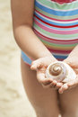 Girl holding seashell on beach midsection of Stock Photo