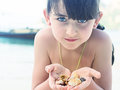 Girl holding seashell caucasian kid with blue eyes seashells on the tropical island Royalty Free Stock Photos