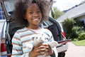 Girl holding toy by car smiling portrait low angle view Royalty Free Stock Photos