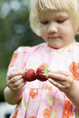 Girl holding two strawberries. Royalty Free Stock Image