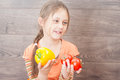 Girl holding vegetables on a wooden background Stock Image