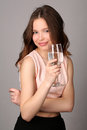 Girl holding wine glass of water. Close up. Gray background Royalty Free Stock Photo