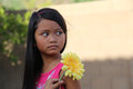 Girl holding yellow flower minority sweating a large looking behind her Stock Photo