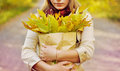 Girl holds a package with leaves yellow Stock Photography