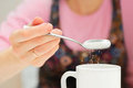 Girl holds a spoon and strews sugar to mug Royalty Free Stock Photos