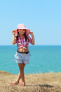Girl holds on to her hat smiling in a and skirt stands with his legs crossed a background of the sea Royalty Free Stock Photo