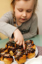 Girl with homemade muffins a cute young trying touching the topping her finger Stock Images