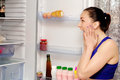 Girl in horror at the open refrigerator near shouts Stock Photos