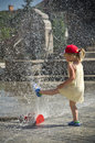 Girl in hot summer city with water sprinkler a cute little having fun on a sunny day a square cooling Stock Photo