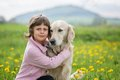 Girl hugging a big dog in an outdoor setting little blond with her pet outdooors park Royalty Free Stock Photo