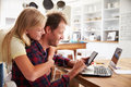 Girl hugging her father, working on laptop at home Royalty Free Stock Photo