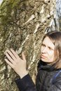 Girl hugging a huge tree trunk in the Park, smiling at the camera. The concept of protection of nature Royalty Free Stock Photo
