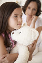Girl hugging teddy bear with mother in background sad young Royalty Free Stock Photo