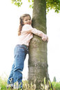 Girl hugging tree in park. Royalty Free Stock Photo