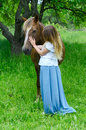 Girl hugs bay horse in apple orchard Royalty Free Stock Photo