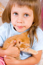 Girl hugs ginger kitten Stock Image