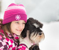 Girl hugs her dog on snow during winter walk in nature Royalty Free Stock Image