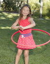 Girl and hula hoop a with long brown hair brown eyes who just lost her two front teeth smiles as she plays with a red on the grass Royalty Free Stock Photo