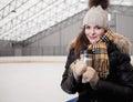 Girl on ice skating rink with mug of hot drink Stock Image