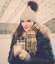 Girl on ice skating rink with mug of hot drink Stock Images