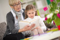 Girl interested looks at the book while grandma read which her grandmother Royalty Free Stock Images