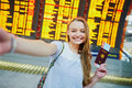 Girl in international airport, taking funny selfie with passport and boarding pass near flight information board Royalty Free Stock Photo