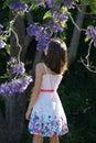 Girl by jacaranda tree Royalty Free Stock Photo
