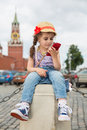 Girl in jeans and cap near the kremlin sitting little on concrete looking into phone hand Royalty Free Stock Photography