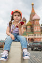 Girl in jeans and cap near the kremlin sitting little on concrete with a phone hand Royalty Free Stock Photos