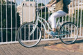 Girl in a jeans jacket and sneakers rides the bridge on a bicycl Royalty Free Stock Photo