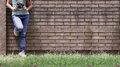 Girl with jeans leaning against the wall Royalty Free Stock Photo