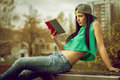 Girl in jeans reading a book on bench young adult sitting park and Stock Photos