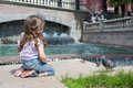 Girl in jeans sits near the fountain and feeding birds cookies Royalty Free Stock Photos