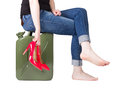 Girl with jerrycan sitting on a red heels in hand Royalty Free Stock Photography