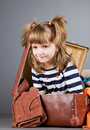 Girl joyfully sits in an old suitcase four year with toys and clothes Royalty Free Stock Images
