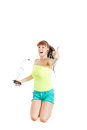Girl jumping in the air with headphones showing thumbs up modern listening to music over mobile phone Stock Image