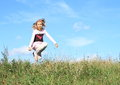 Girl jumping in grass little kid happy smiling of green meadow with blue sky behind Stock Photos