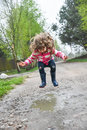 Girl jumping in a paddle Royalty Free Stock Photo