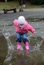 Girl jumping in puddles at autumn Stock Images