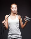 Girl with jumping rope on dark background young attractive caucasian in white sportswear Royalty Free Stock Photo