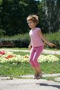 Girl jumping on a skipping rope in the park Stock Photography
