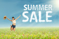 Girl jumping with summer sale sign pretty on the park cloud design of Stock Photo