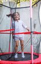 Girl jumping in the trampoline little on Royalty Free Stock Photo