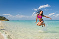 Girl jumping in the water at the beach of koh ngai island thailand Stock Photos