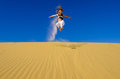 Girl jumping on the yellow sand dune Royalty Free Stock Photo