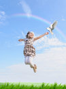 Girl jumps with dove in hand outdoors Royalty Free Stock Image