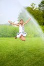 Girl jumps under spray drops little Royalty Free Stock Photography