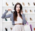 Girl keeps credit card in footwear shop woman holds with great variety of stylish shoes Royalty Free Stock Photos