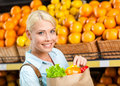 Girl keeps paper bag with fresh vegetables hands against the shelves of fruits in the shopping mall Royalty Free Stock Photo